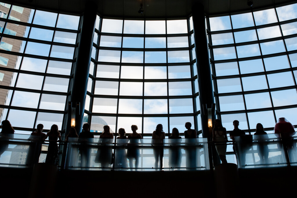 Picture of seniors on an upper level silhouetted in front of a large window at Cornish College Commencement at McCaw Hall
